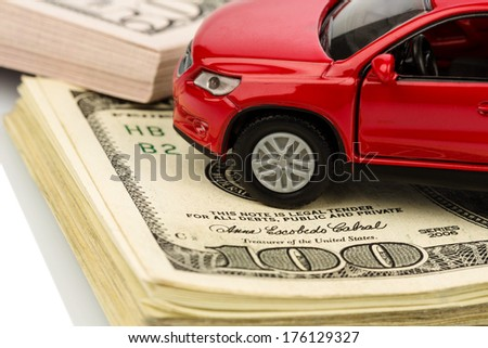 a car stands on dollar banknotes. cost of buying a car, fuel, insurance and other car costs - stock photo