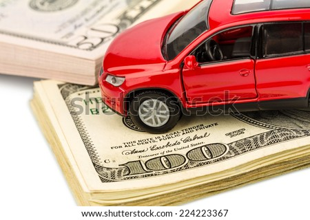 a car stands on dollar banknotes. costs for the purchase of automobiles, gasoline, insurance and other car costs - stock photo