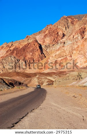 A car travels along the curved road next to the variegated slopes of Artists Palette in Death Valley, California. Various mineral pigments have colored the volcanic deposits found here. - stock photo