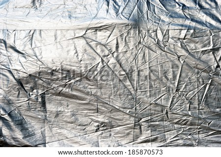 A car with cover sheet for sunlight, rain and dust protection   - stock photo