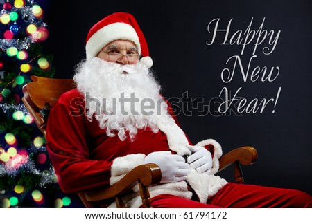 A card with Santa sitting in the armchair at the Christmas tree and the text ?Happy New Year? - stock photo
