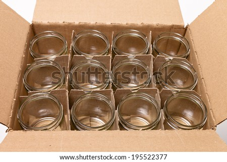 A cardboard box of clean, empty glass jars  with no lids. - stock photo