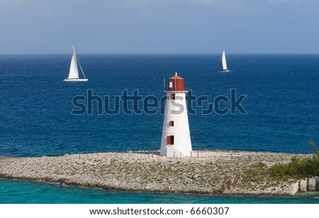 A Caribbean Lighthouse With Sailboats - stock photo