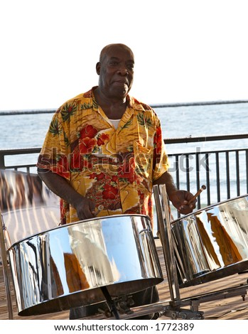 A caribbean musician playing steel drums. - stock photo
