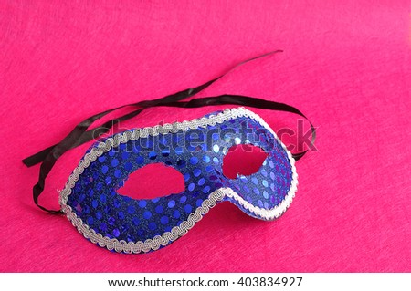 A carnival mask displayed on a pink background - stock photo