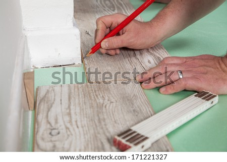 A Carpenter is measuring and marking the Laminate before sawing. - stock photo