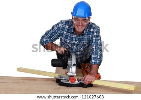 A carpenter with a circular saw. - stock photo