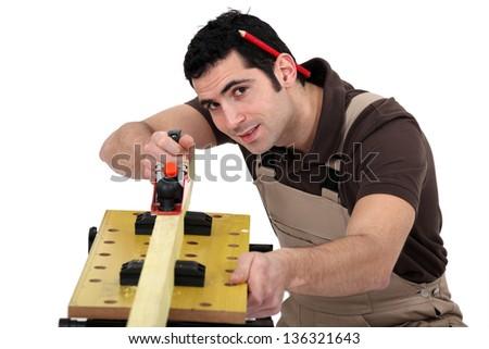 A carpenter with a plane. - stock photo