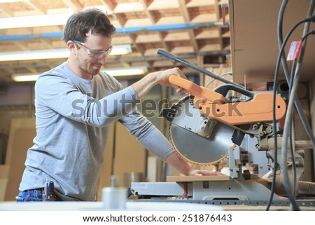 A Carpenter working hard at the shop - stock photo