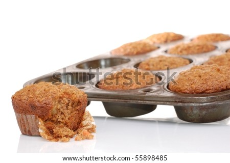 A Carrot Muffin with a Bite Taken Out of it with a Muffin Tin in the Background - stock photo