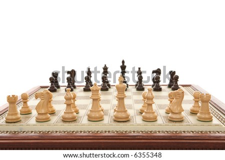 A carved marble chess board and wooden chess pieces.  Focus to foreground. - stock photo