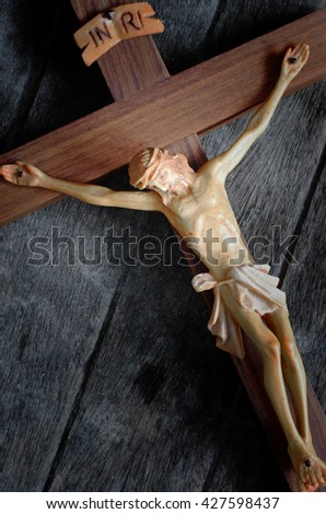 A carved statue of the Crucifixion of Jesus Christ on wood background in vintage style - stock photo