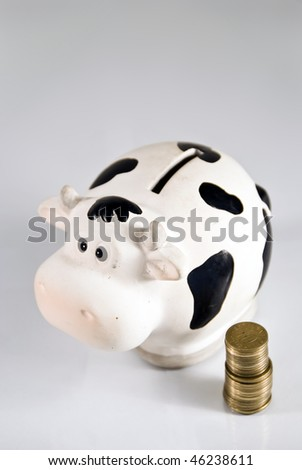 A cash cow/piggy bank, coins on the side, with copy-space - stock photo