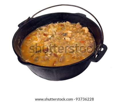 a caste iron pot of seafood gumbo on a white background - stock photo