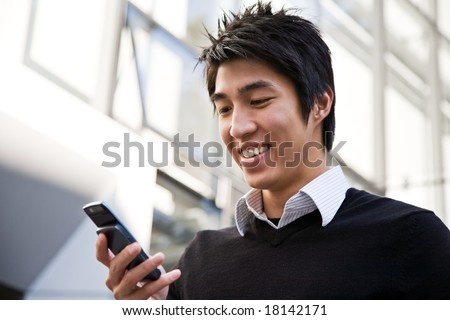A casual asian businessman texting on his cell phone - stock photo