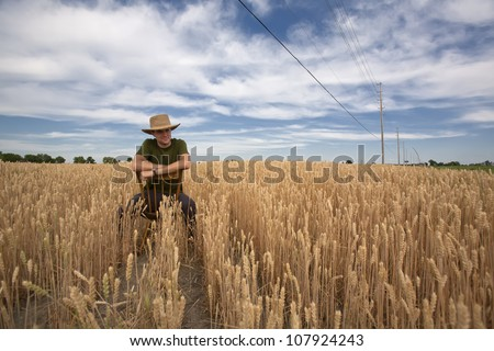 A casual portrait of a farmer sitting on an old wooden chair in his wheat field on a nice summers day. - stock photo