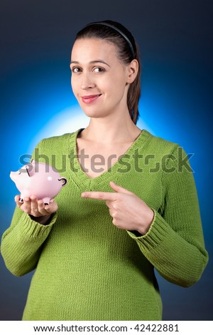 A casually dressed young woman showcasing her savings bank. - stock photo