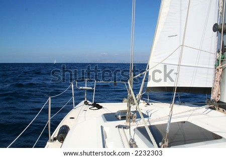 A catamaran sailboat on the open sea. - stock photo
