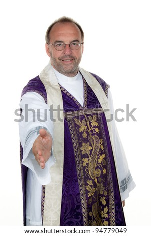 a catholic priest extends his hand in greeting. - stock photo