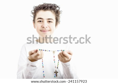A Caucasian boy holds Rosary beads with both hands: Rosary includes a picture of Our Lady of Medjugorje, the Blessed Virgin Mary - stock photo