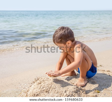 A caucasian child boy playing with sand in the beach - stock photo