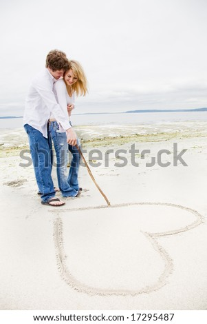 A caucasian couple in love drawing a heart sign on the beach - stock photo