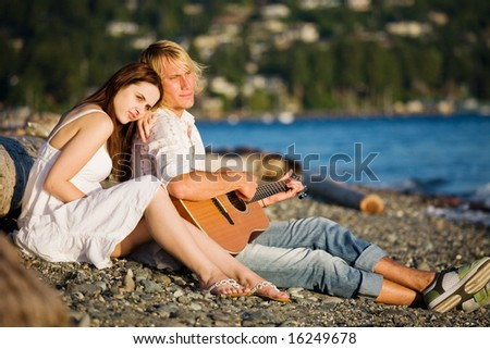 A caucasian couple sitting on the beach playing guitar - stock photo