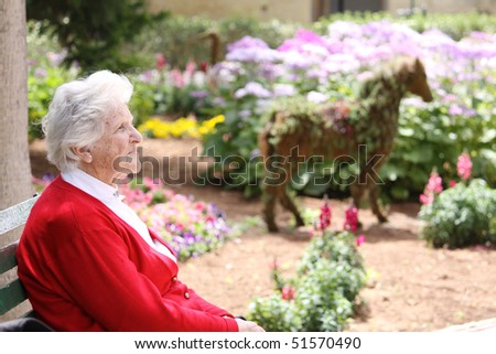a caucasian elderly woman sitting on a park bench in the sun - stock photo