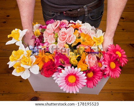 A caucasian male holding a cardboard box full of flowers. - stock photo