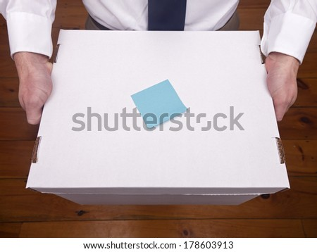 A caucasian male holding an office box with a blue note on top. - stock photo