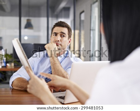 a caucasian male interviewer looking skeptical while listening to an asian female interviewee. - stock photo