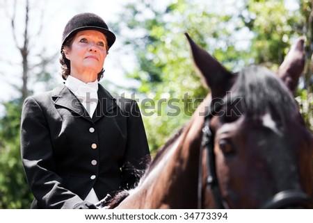 A caucasian senior woman riding a horse outdoor - stock photo