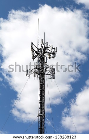 A cellular antenna tower isolated over a blue sky with white fluffy clouds. - stock photo