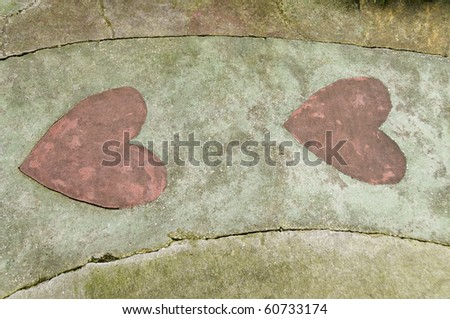 A cement walkway with two red heart shapes. - stock photo