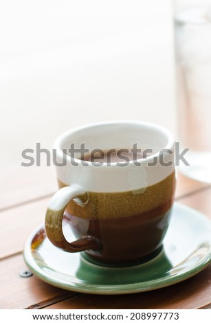 A ceramic cup of hot coffee on wooden table. - stock photo