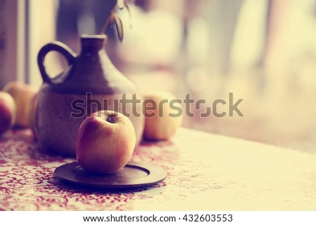 A ceramic jug, pitcher with water, apples and talavera table in soft light, summer table decoration - stock photo