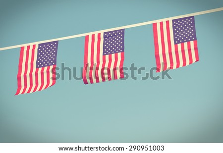A chain / garland/ bunting of USA flags hanging proudly for July 4 Independence Day - vintage / retro / Instagram processed - stock photo