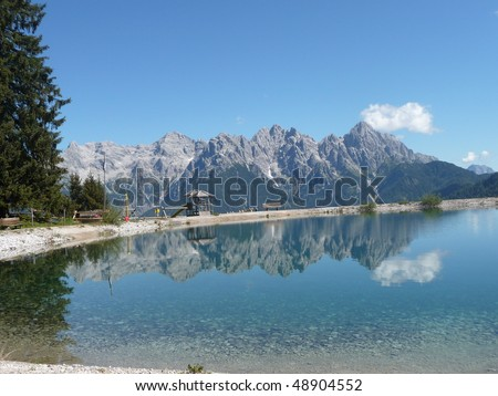 A chain of alps is mirroring in the lake - stock photo