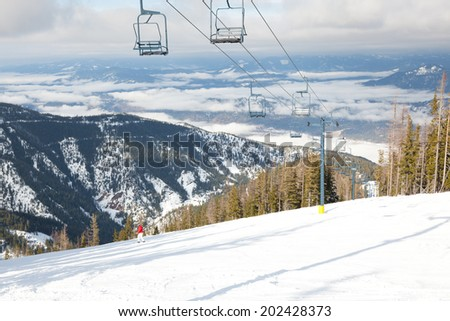 A chair lift for a winter ski resort goes up the side of a snowy mountain with a valley view and lone skier. - stock photo