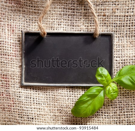 a chalkboard on a textile coffee bag with basil - stock photo