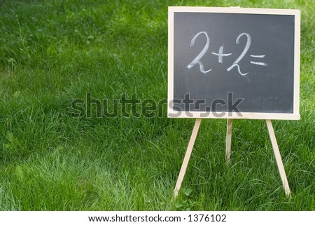"""A chalkboard standing in the grass and with """"2+2="""" written on it. - stock photo"""