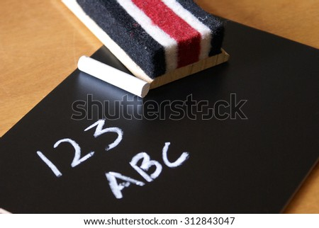 A chalkboard with an eraser and white chalk. - stock photo