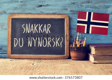 a chalkboard with the question snakkar du nynorsk?, do you speak Norwegian? written in Norwegian, a pot with pencils, some books and the flag of Norway, on a wooden desk - stock photo
