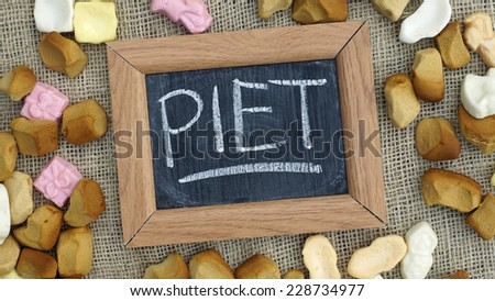 A chalkboard with the text Piet and a pile of Pepernoten, typical Dutch treat for Sinterklaas on 5 december - stock photo