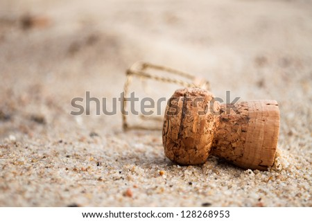 A champagne cork left in the sand - stock photo