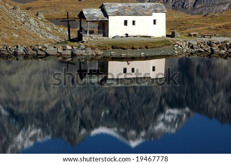 A chapel reflected in the Schwarzsee (black lake) on the shoulders of the Matterhorn in the Swiss Alps.  The surface of the lake is still which allows reflections of the mountains and - stock photo