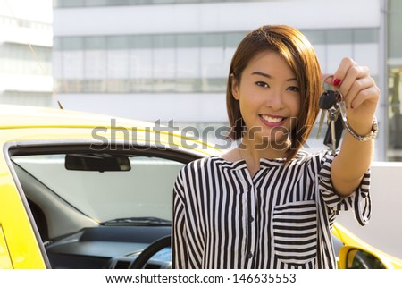 A charming Asian lady standing in front of her car showing her car keys. - stock photo