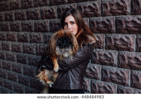 a charming young brunette woman holding a small dog Pekingese, closeup portrait, dark. Friendship between dogs and people - stock photo