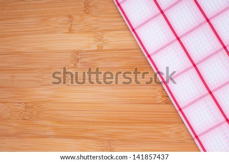 A Checkered Kitchen Towel Laying on Bamboo Cutting Board or Counter Top with Room for your words or text.  Horizontal or Vertical. - stock photo