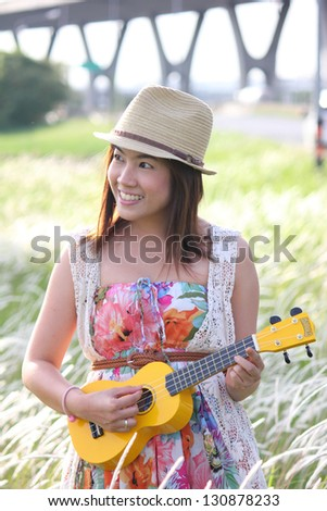 A cheerful asian girl with her ukulele in a meadow - stock photo